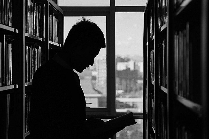 Silhouette of man searching in library