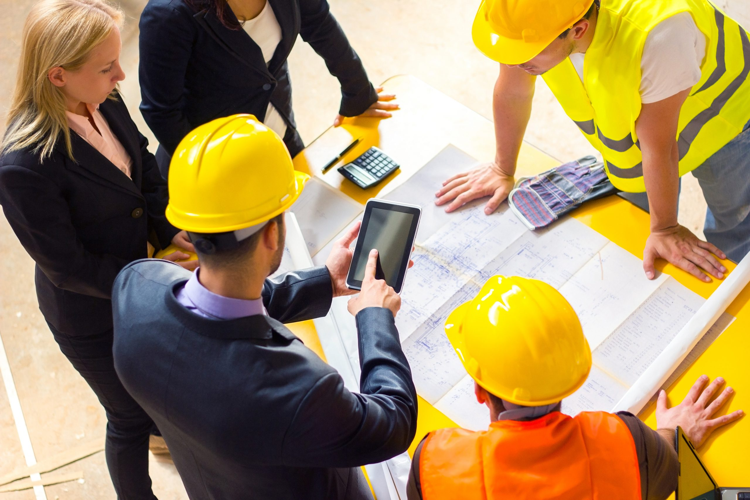 Construction workers leaning over architectural drawings with mobile device